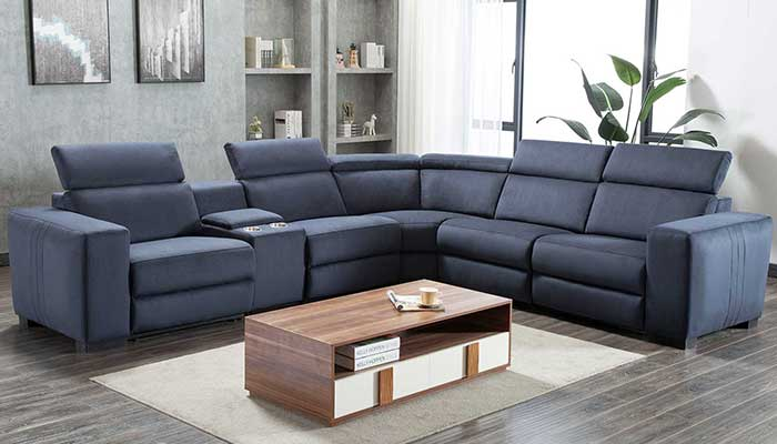 5 seater blue sectional with recliner foot rest with white rug and wood coffee table