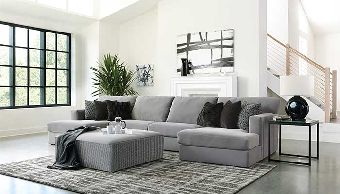 grey sectional with grey ottoman with black accent pillows