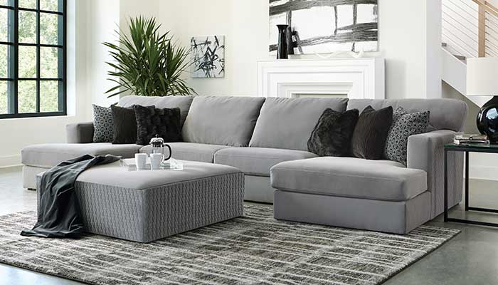 Grey Velvet Sectional and ottoman with black accent pillows