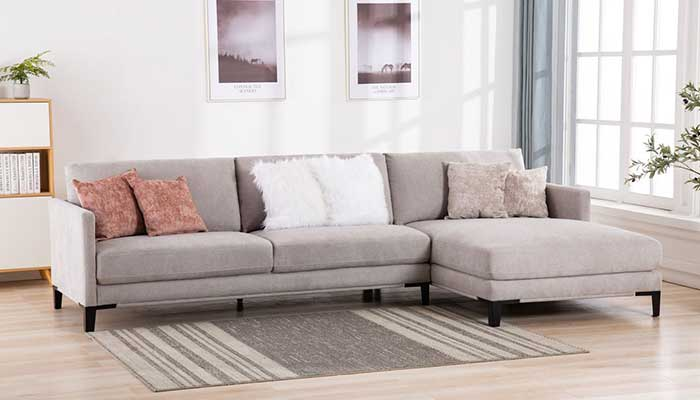 grey chaise sectional with orange white and beige accent pillows
