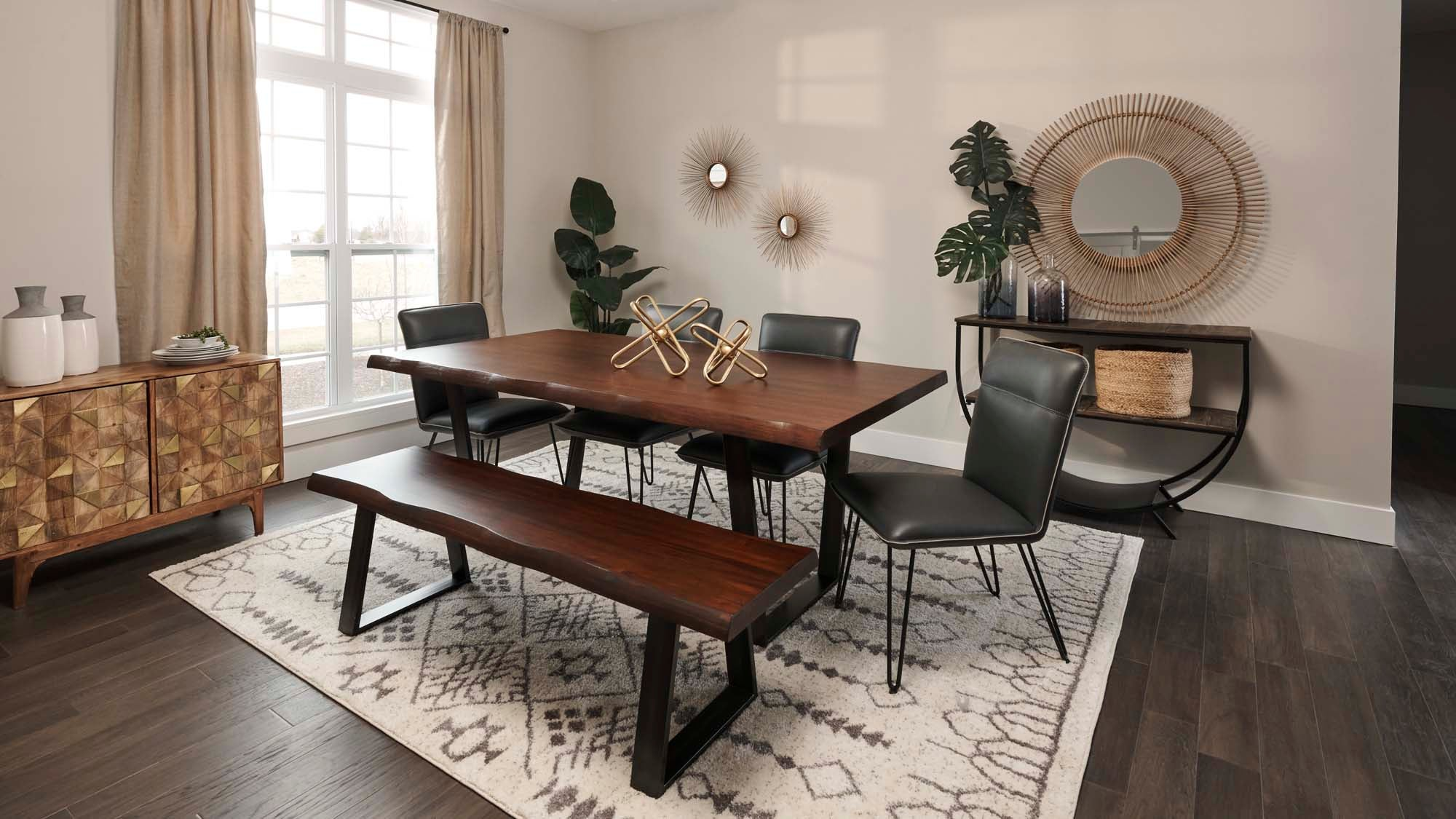 white patterned rug with dark brown farmhouse dining table with bench and 4 black chairs