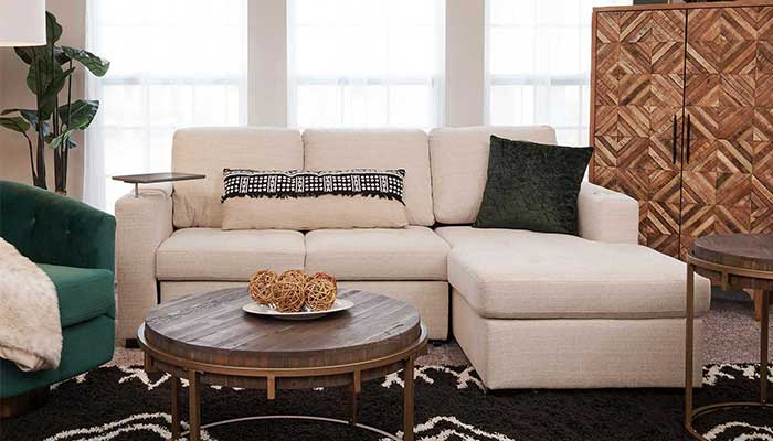 white 3 seater sectional next to a green accent chair and circular coffee table