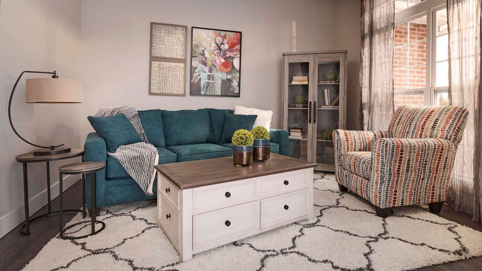 white rug with a torquise soft and multi colored chair and a white wooden coffee table