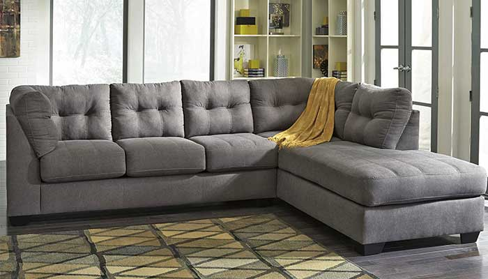 4 seater grey fabric sectional with yellow throw