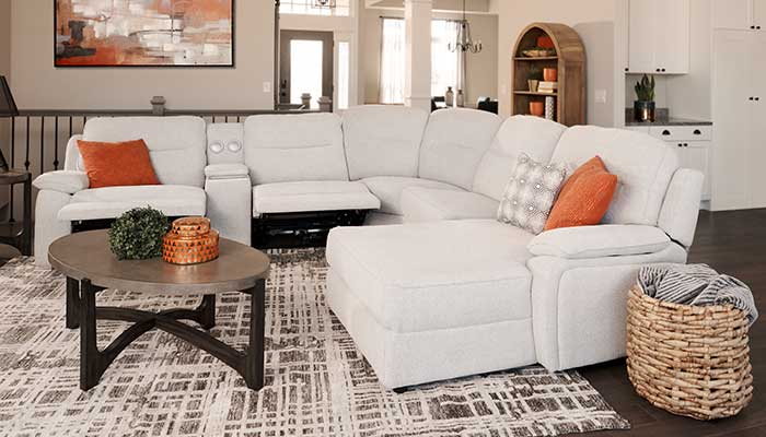 white power sectional with orange accent pillows on top of a white and grey patterned rug