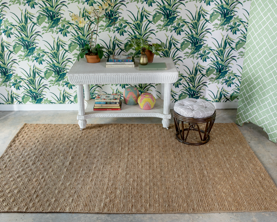 light brown textured rug next to green plant patterned wallpaper