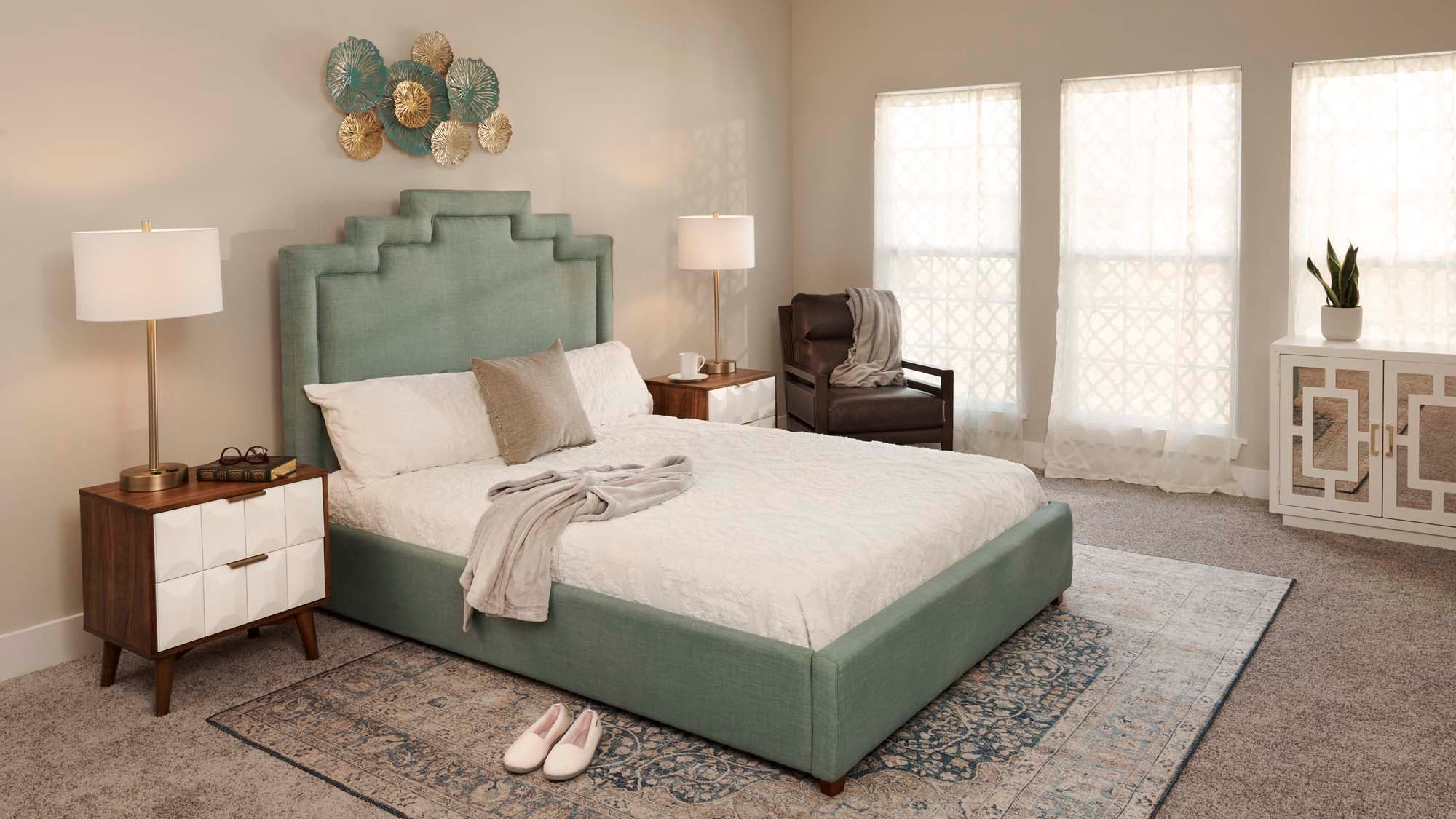 grey rug in bedroom with green bedframe and white comforter