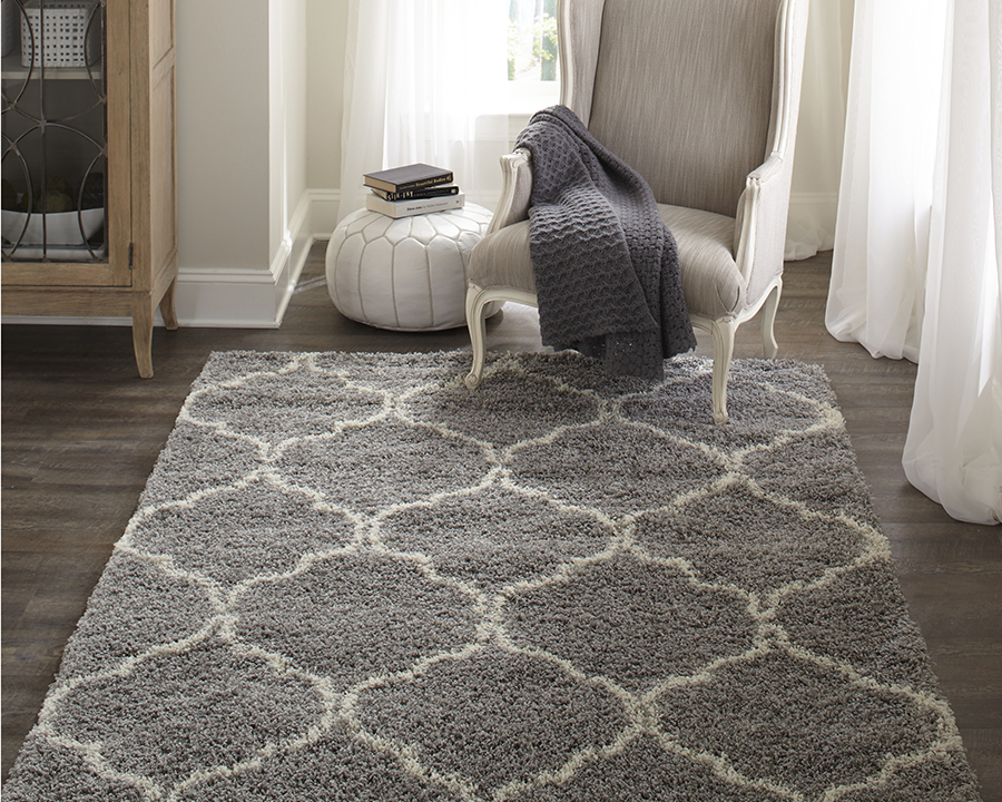 gray patterned synthetic rug with a white accent chair and a grew throw