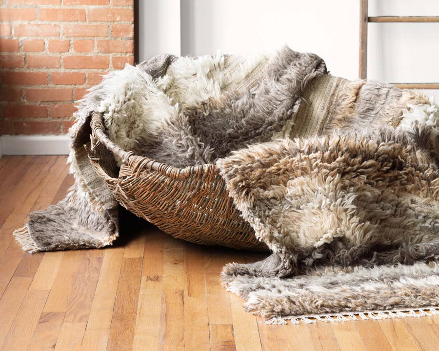 grey brown and white wool rug in a basket on a wood floor