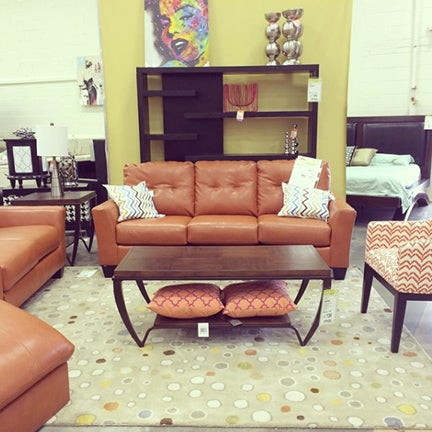Orange leather couch on light brown polka dot rug